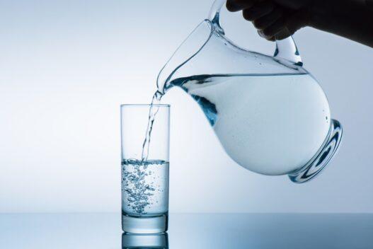 Glaskande der hælder vand i et glas